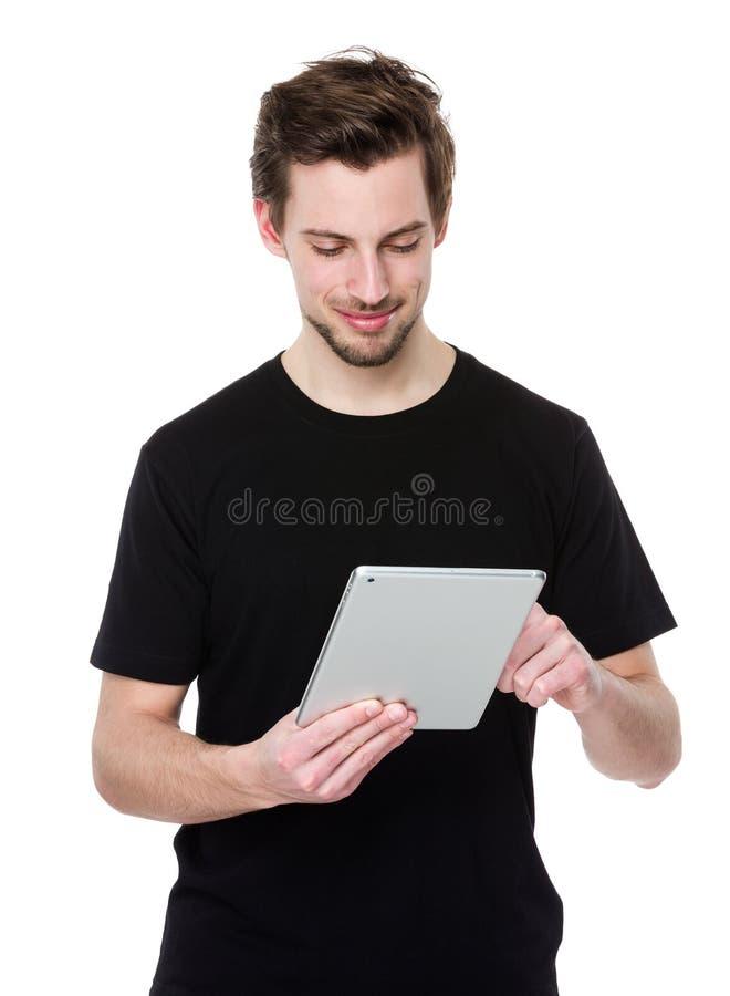 Ung man som rymmer en PC för minnestavla för handlagblock arkivfoton