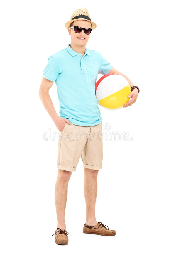 Ung man som rymmer en strandboll royaltyfria bilder