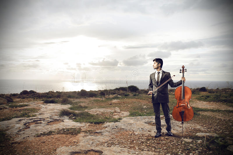 Ung man som rymmer en violoncell arkivfoton