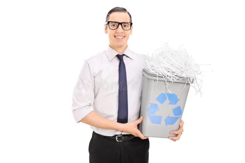 Ung man som rymmer ett återanvändningsfack fullt av strimlat papper royaltyfri foto