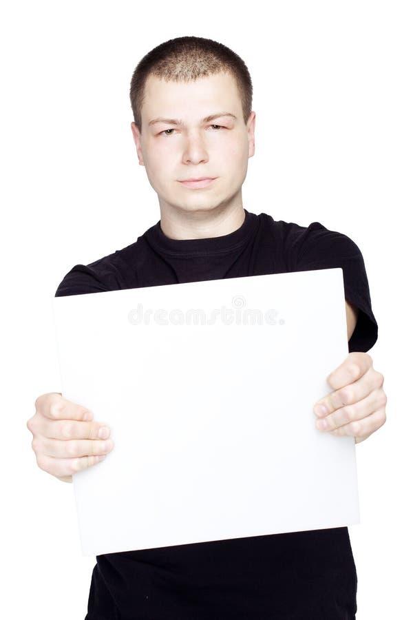 Ung man som rymmer ett tomt ark tomt på isolerad vit bakgrund royaltyfria foton