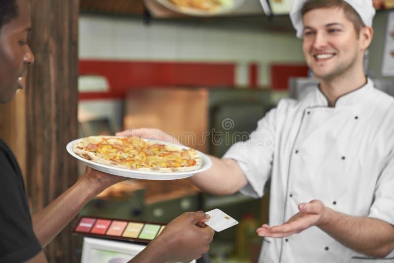 Ung man som rymmer läcker pizza och betalar med kortet royaltyfria foton