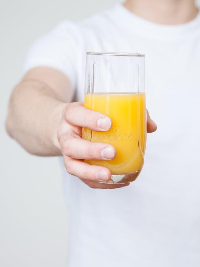 Ung man som rymmer orange fruktsaft royaltyfri bild