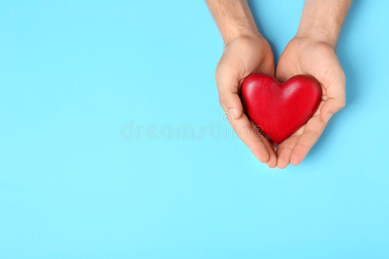 Ung man som rymmer röd hjärta på ljust - blå bakgrund, bästa sikt med utrymme för text royaltyfria foton