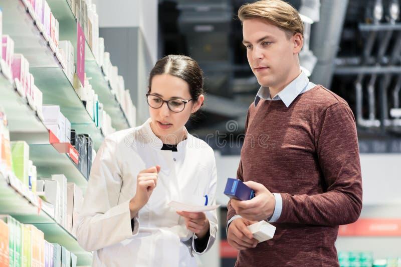 Ung man som rymmer två mediciner, medan se olika produkter arkivbild