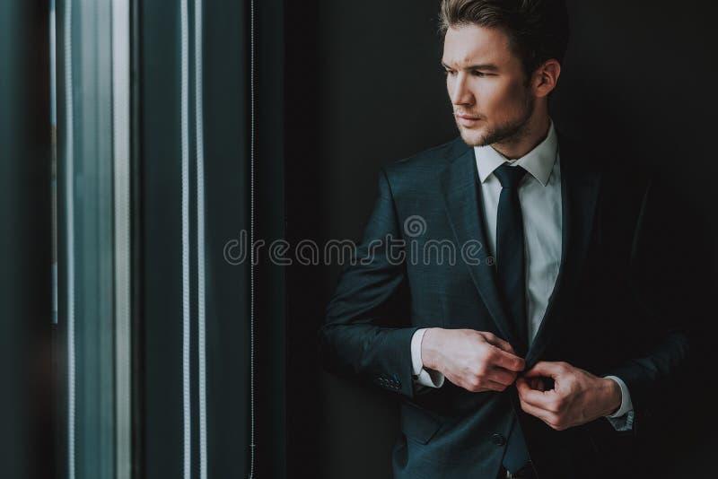 Ung man som rynkar pannan, medan knäppas hans omslag royaltyfri bild