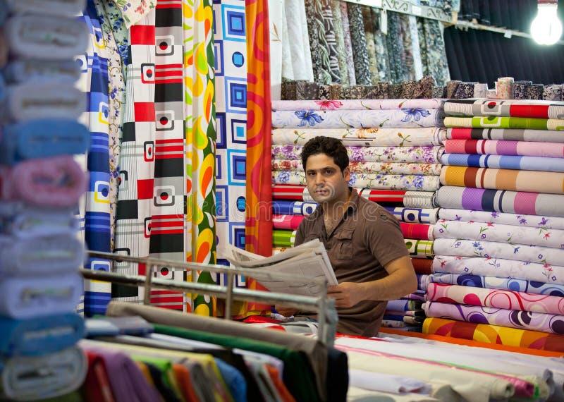 Ung man som säljer tyger i traditionell basar av Teheran royaltyfri foto