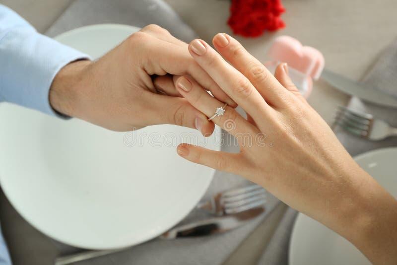 Ung man som sätter förlovningsringen på fästmös finger på det romantiska datumet arkivbild