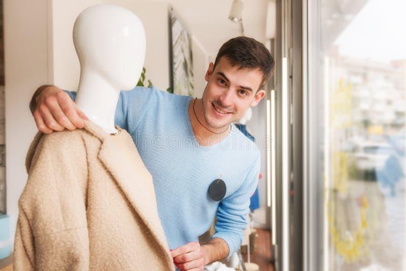 Ung man som sätter kläder på en skyltdocka i lager royaltyfria bilder