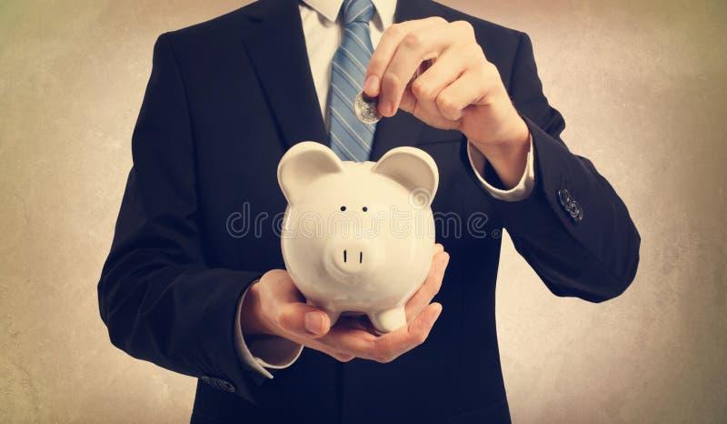 Ung man som sätter in pengar i spargrisen royaltyfria foton