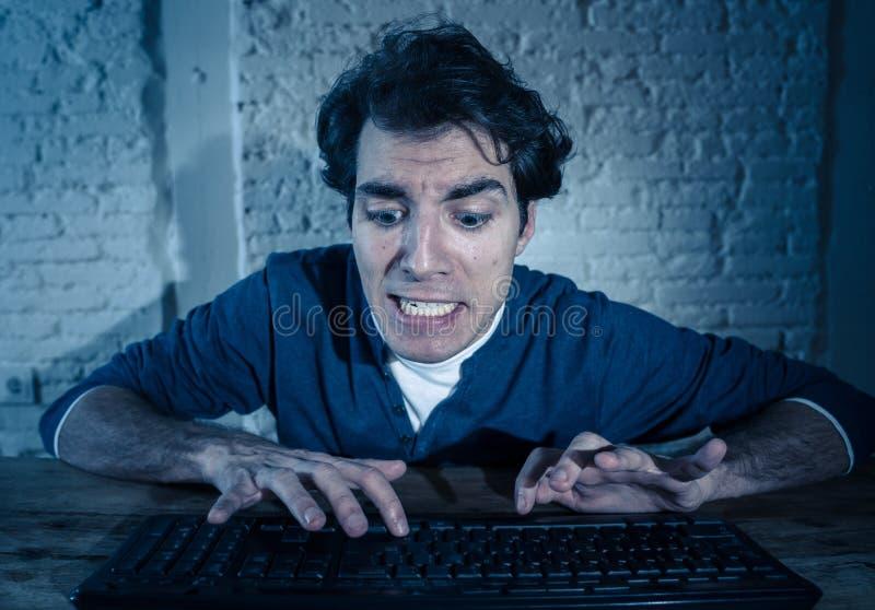 Ung man som sent hakas p? datorb?rbara datorn p? natten som k?nner sig stressad och s?mnl?s fotografering för bildbyråer