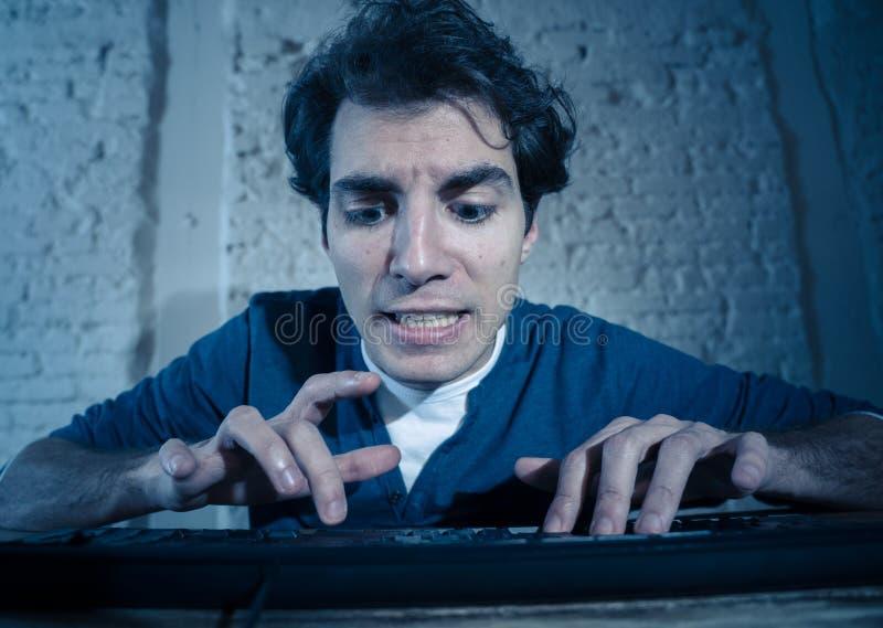 Ung man som sent hakas p? datorb?rbara datorn p? natten som k?nner sig stressad och s?mnl?s arkivfoton