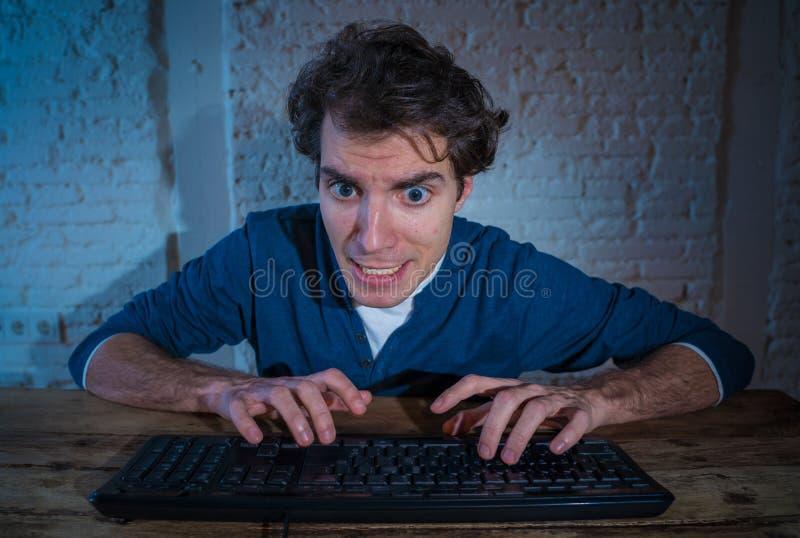 Ung man som sent hakas p? datorb?rbara datorn p? natten som k?nner sig stressad och s?mnl?s royaltyfria bilder