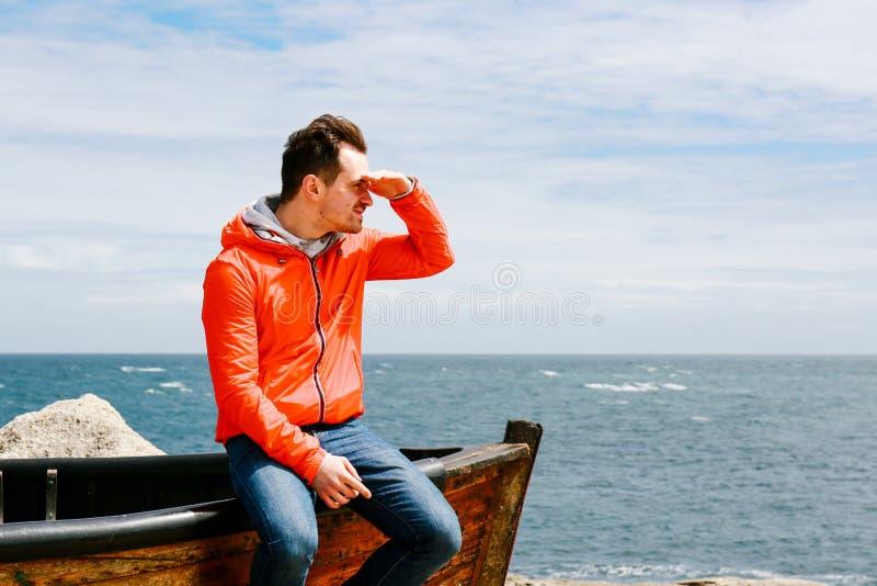 Ung man som ser avståndet, hand på pannan royaltyfri foto
