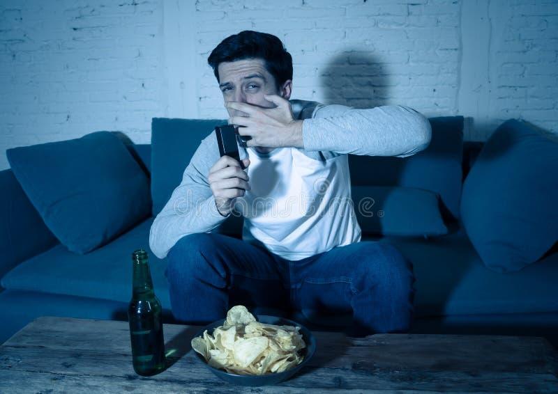 Ung man som ser förskräckt sammanträde på hållande ögonen på TV för soffa på natten I mänskliga reaktioner och sinnesr royaltyfri fotografi