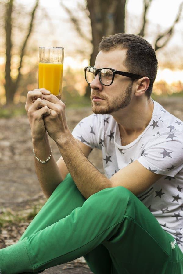 Ung man som ser förvirrad på exponeringsglaset med fruktsaft arkivbilder