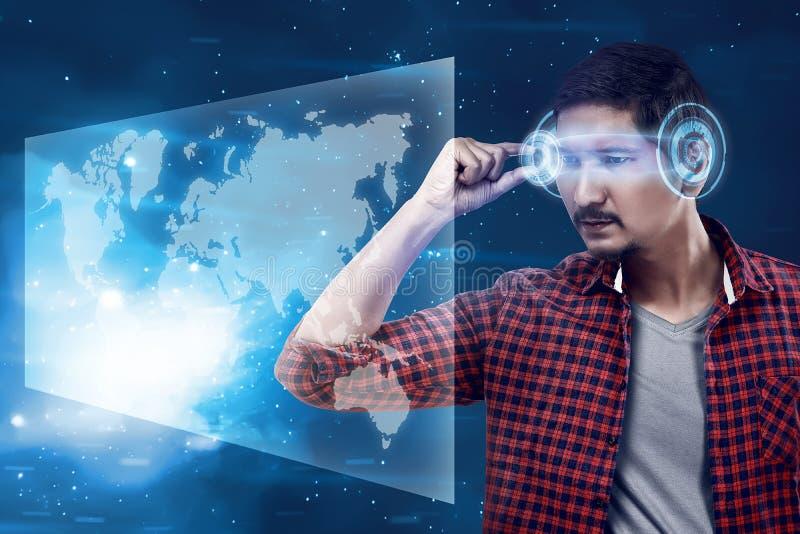 Ung man som ser världskartan med futuristiska smarta tekniskt avancerade glas royaltyfri foto