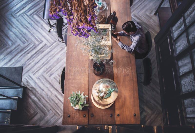 Ung man som sitiing till att arbeta på Smartphone i coffee shop Överkant v arkivfoton