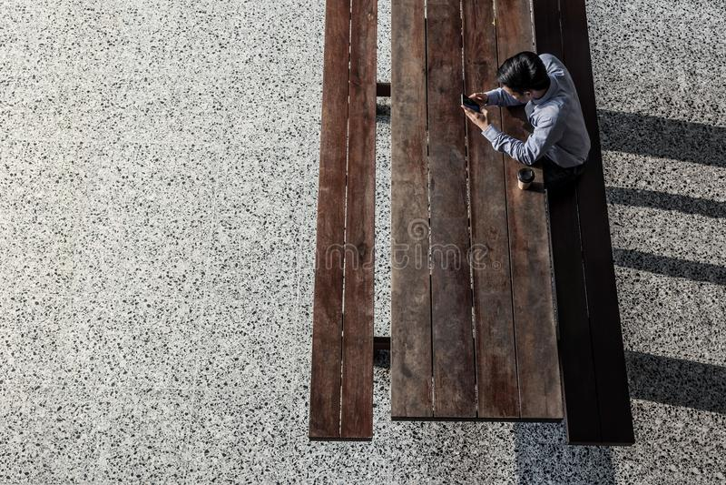Ung man som sitiing till att arbeta på Smartphone i högskola Top beskådar royaltyfri bild