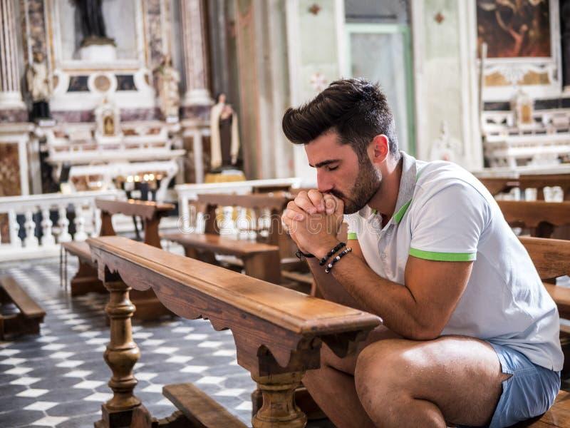 Ung man som sitter, i att be f?r kyrka arkivfoton