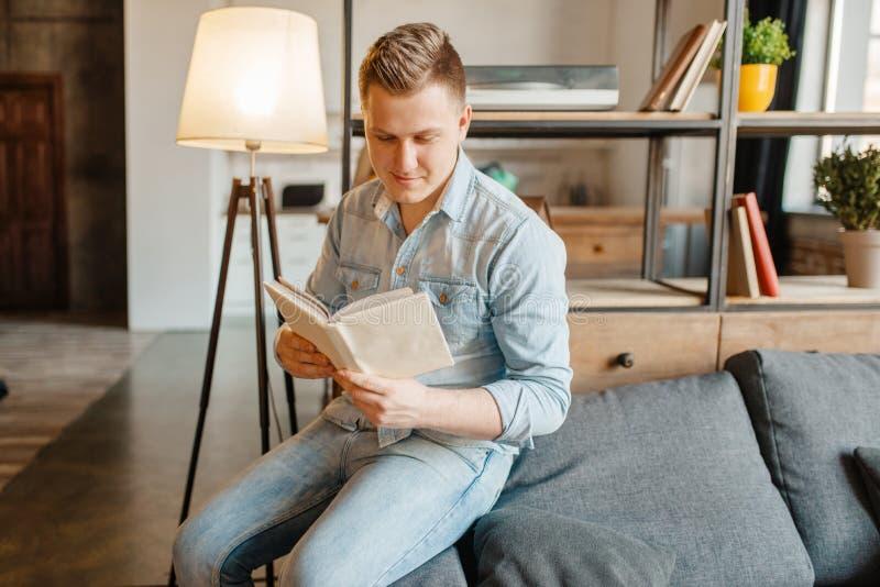 Ung man som sitter i soffa och läser en bok royaltyfri foto