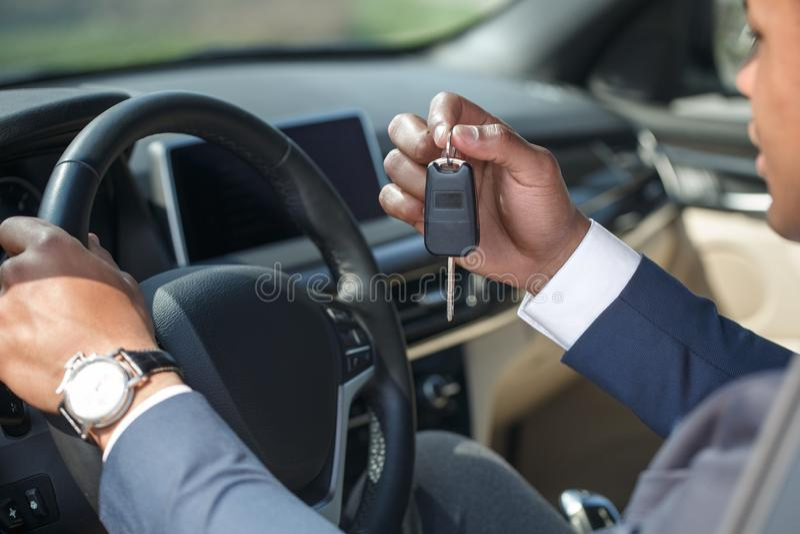 Ung man som sitter inom bilen med nyckel- närbild för innehavstyrhjul royaltyfri fotografi