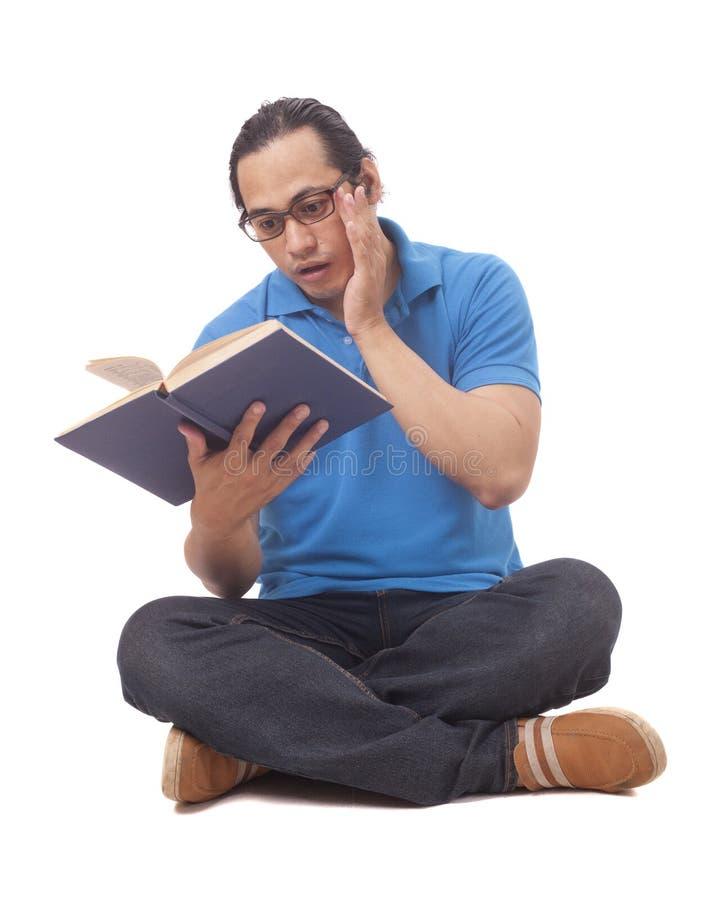 Ung man som sitter på golv och läser en bok, chockad gest arkivbild
