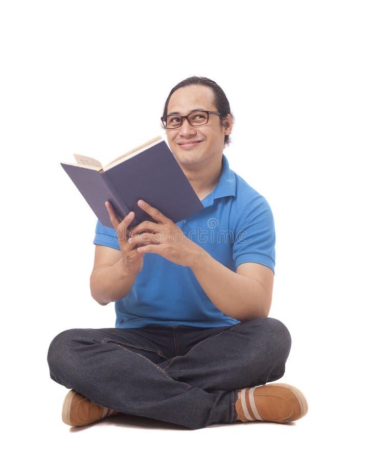 Ung man som sitter på golv och läser en bok, tänkande gest fotografering för bildbyråer