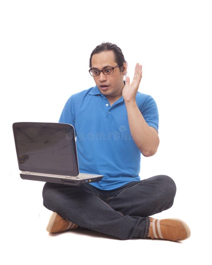 Ung man som sitter på golv och skriver på bärbara datorn, chockad gest royaltyfria bilder