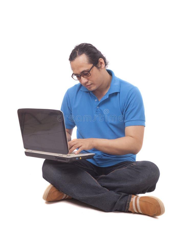 Ung man som sitter på golv och skriver på bärbara datorn arkivfoton