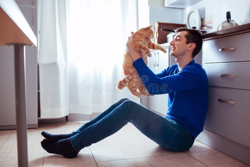 Ung man som sitter på golvet av köket med en katt royaltyfri bild