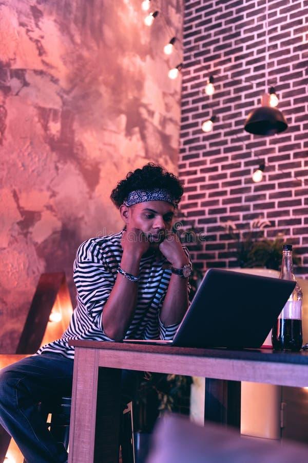 Ung man som sitter på tabellen och den hållande ögonen på videoen på en bärbar dator, medan tänka om något arkivbild