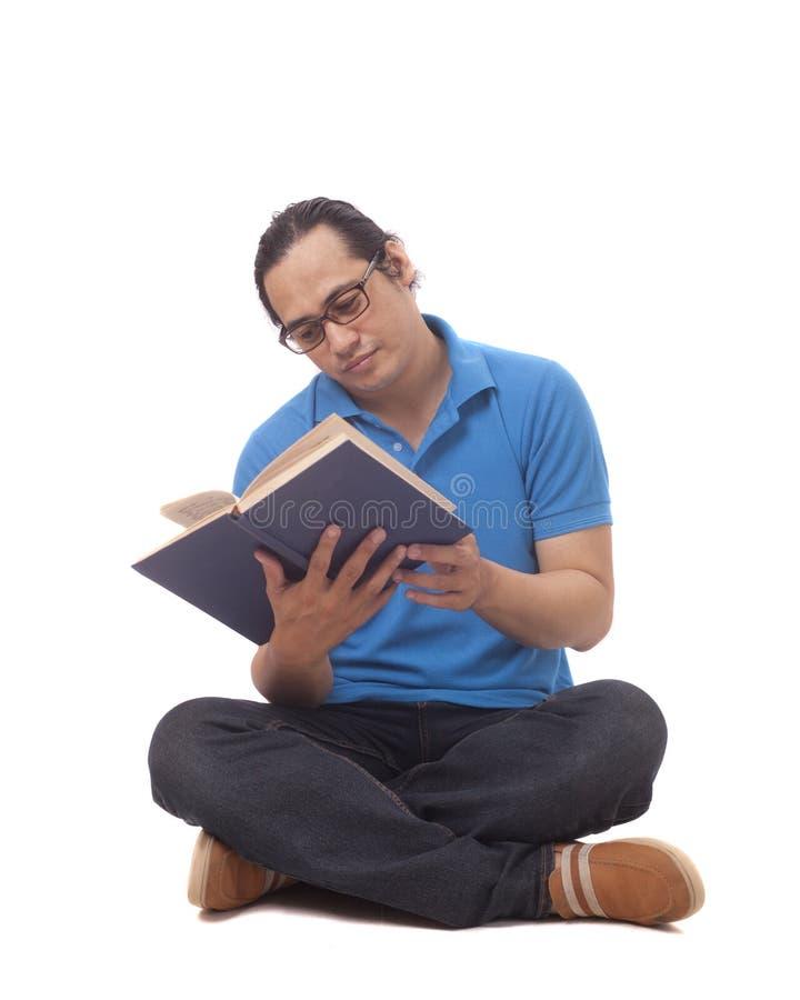 Ung man som sitter p? golv och l?ser en bok royaltyfri foto