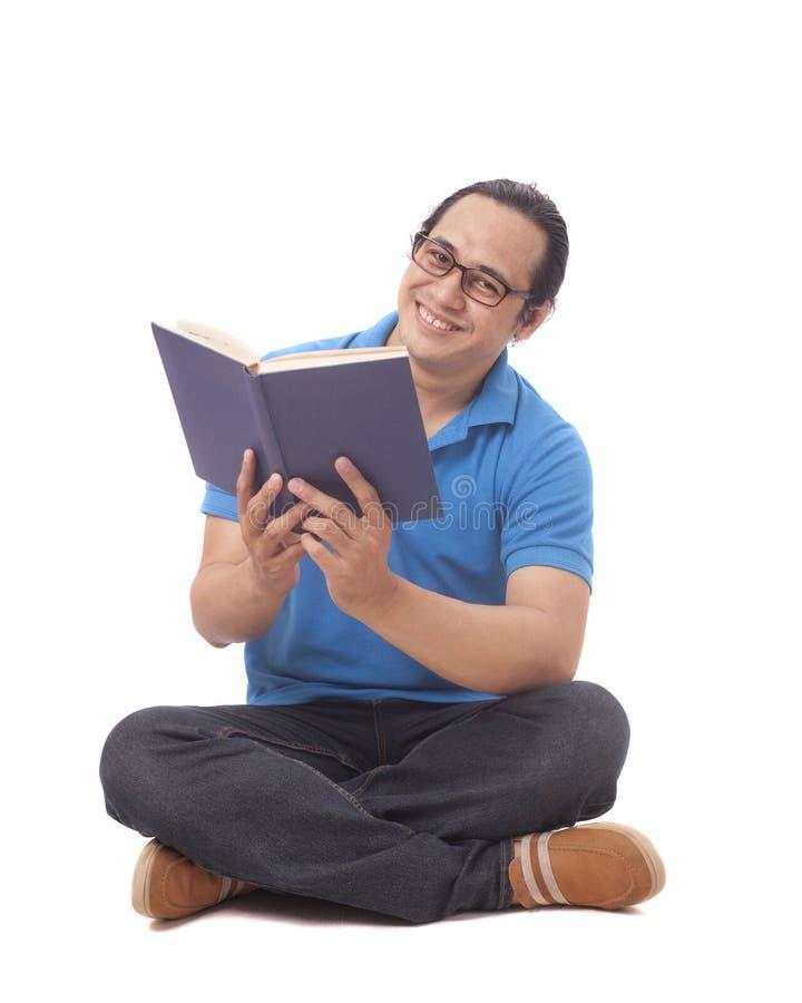 Ung man som sitter p? golv och l?ser en bok arkivfoto