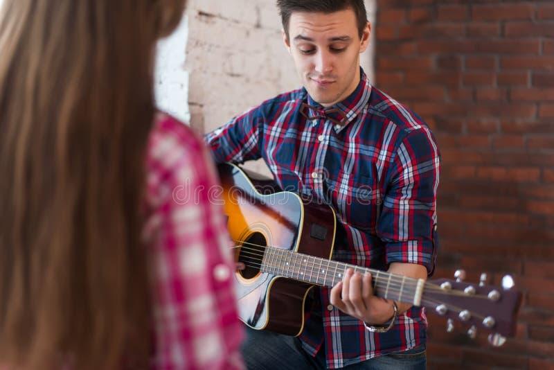 Ung man som sjunger spela gitarren för hans flickvän royaltyfria bilder