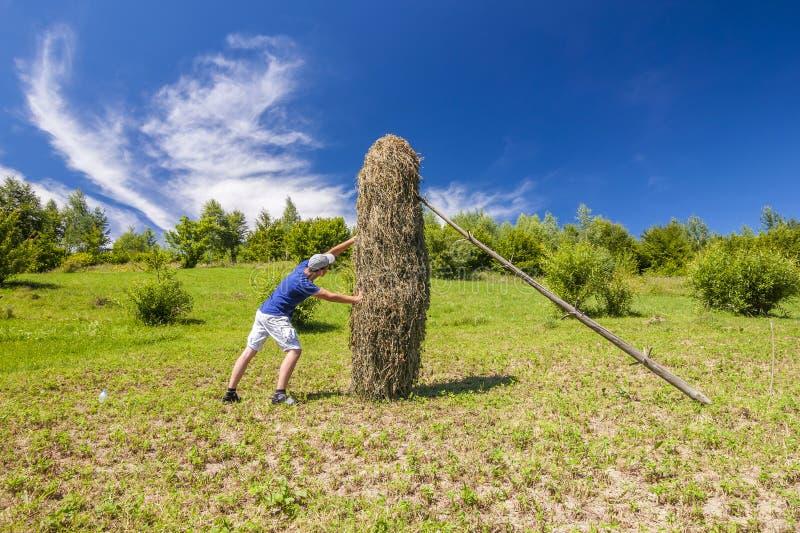 Ung man som skjuter mot en höstack på en solig sommardag royaltyfri fotografi