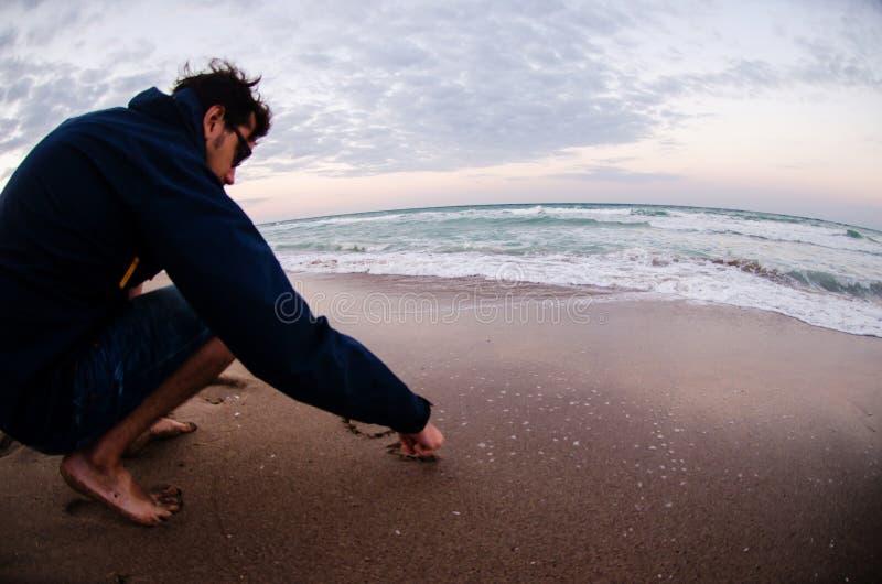 Ung man som skriver ett meddelande i seanden på havet arkivbild