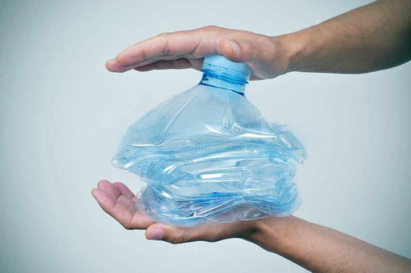 Ung man som slår en plast- flaska med hans händer royaltyfri foto