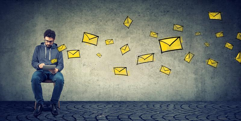 Ung man som smsar på minnestavlan som överför emails, medan posera på grå färger fotografering för bildbyråer
