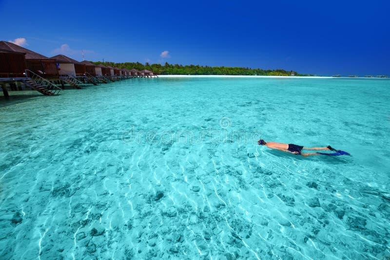 Ung man som snorklar i den tropiska ön med overwaterbungalower royaltyfri fotografi