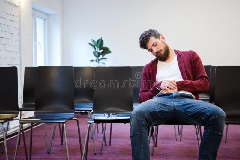Ung man som sovande faller på konferensrum royaltyfri foto