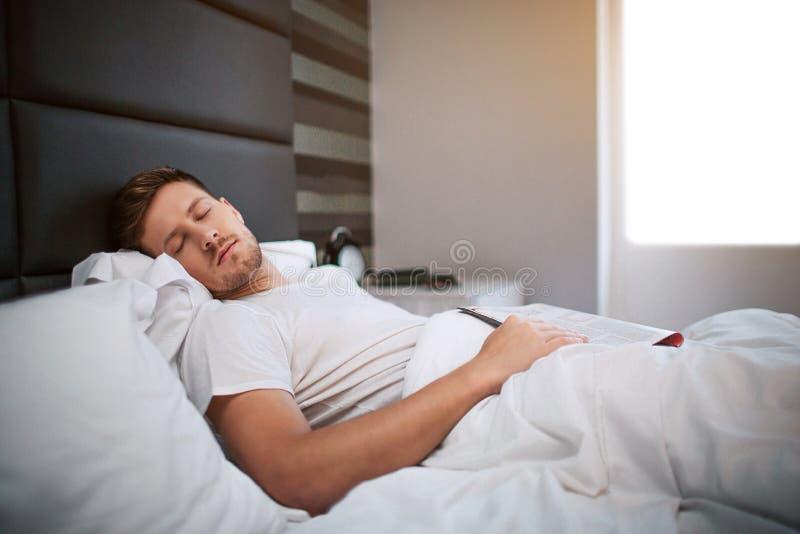 Ung man som sover i säng i morgonen lugnat fridsamt ovanför den härliga naturen för morgonen för guld för fågeloklarhetsfärger ti royaltyfri bild
