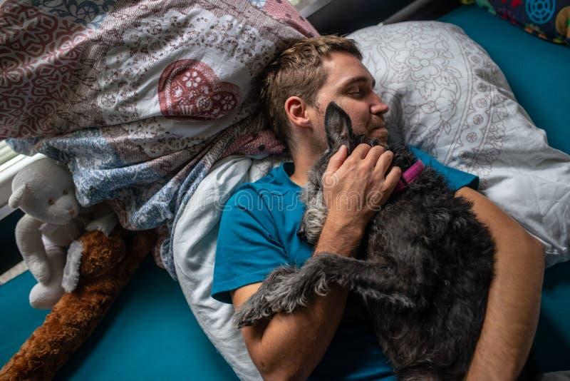 Ung man som sover och kelar med hans hund royaltyfri fotografi