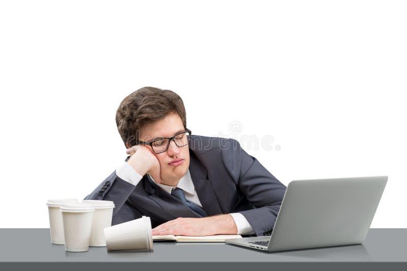 Ung man som sover på arbetsplatsen fotografering för bildbyråer
