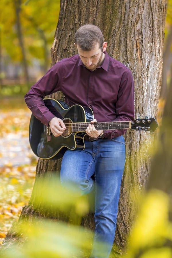 Ung man som spelar den akustiska gitarren utomhus royaltyfri fotografi