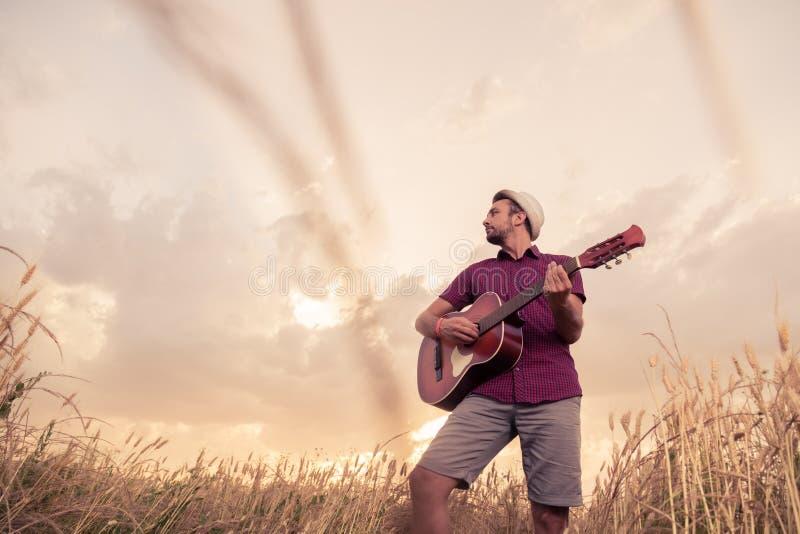 Ung man som spelar den akustiska gitarren utomhus royaltyfri foto