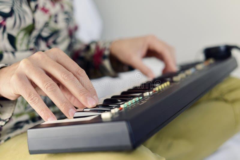 Ung man som spelar ett elektroniskt tangentbord fotografering för bildbyråer