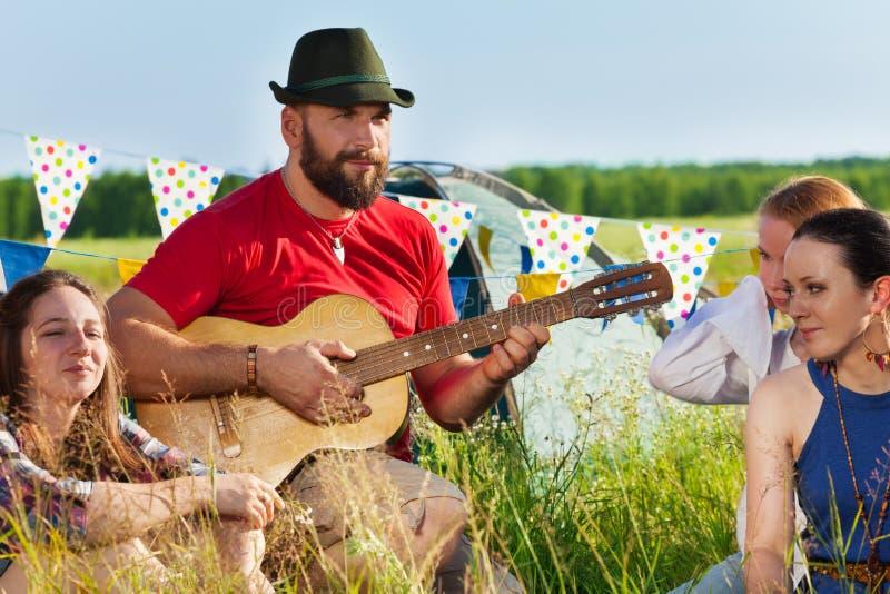 Ung man som spelar gitarren för hans vänner i läger arkivbild