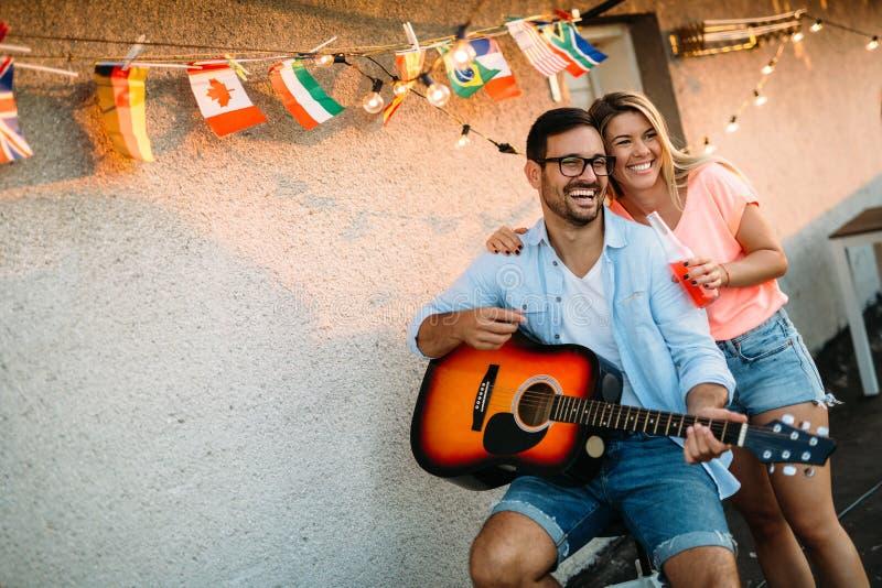 Ung man som spelar gitarren för vänner och hans flickvän royaltyfri bild