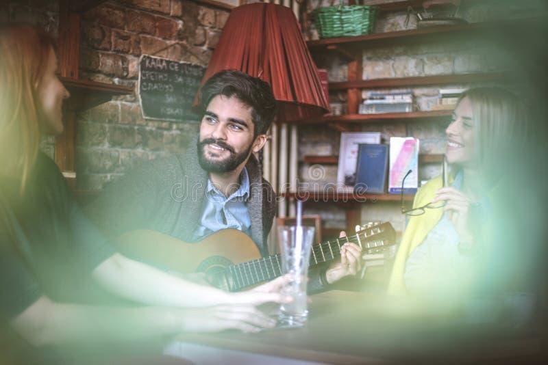 Ung man som spelar gitarren i kafé till hans vänner royaltyfria foton